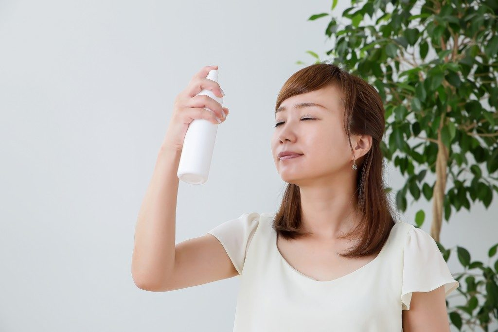 Woman applying facial mist
