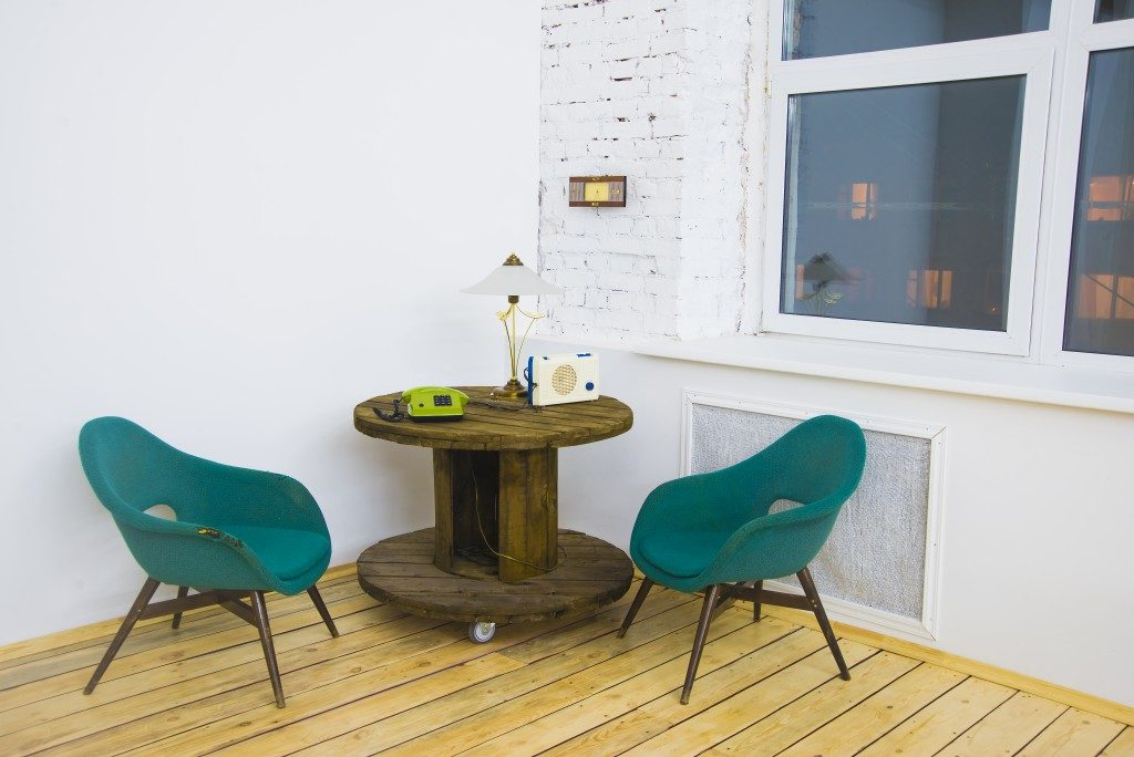 green chair with recycled wooden circle table and phone, lamp, radio on table