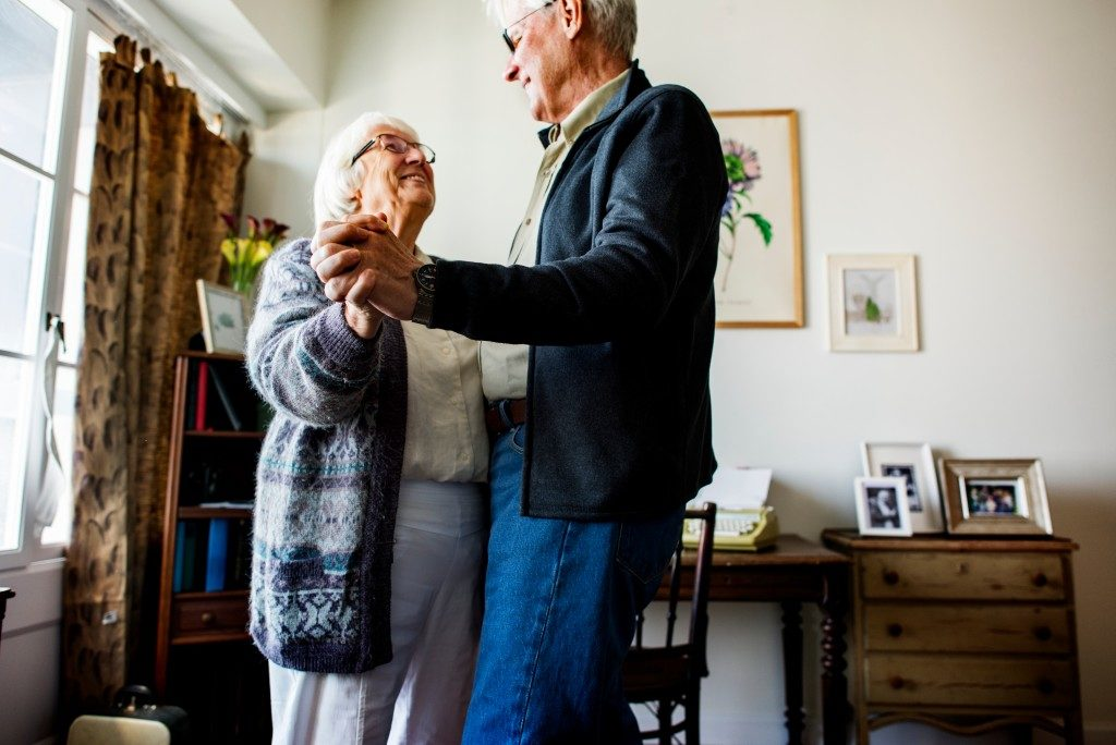 Old couple dancing in the living room