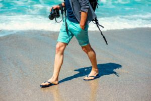 Man holding a camera walking at the beach