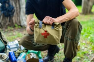 man holding a bag of first aid kit in the camping site