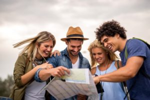 Friends on vacation looking at map