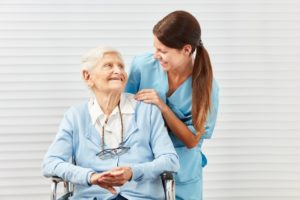 nurse and older woman smiling at each other