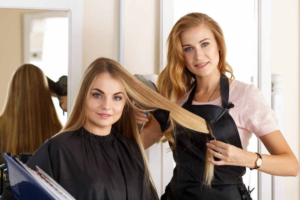 woman with blonde hair getting keratin treatment at the salon