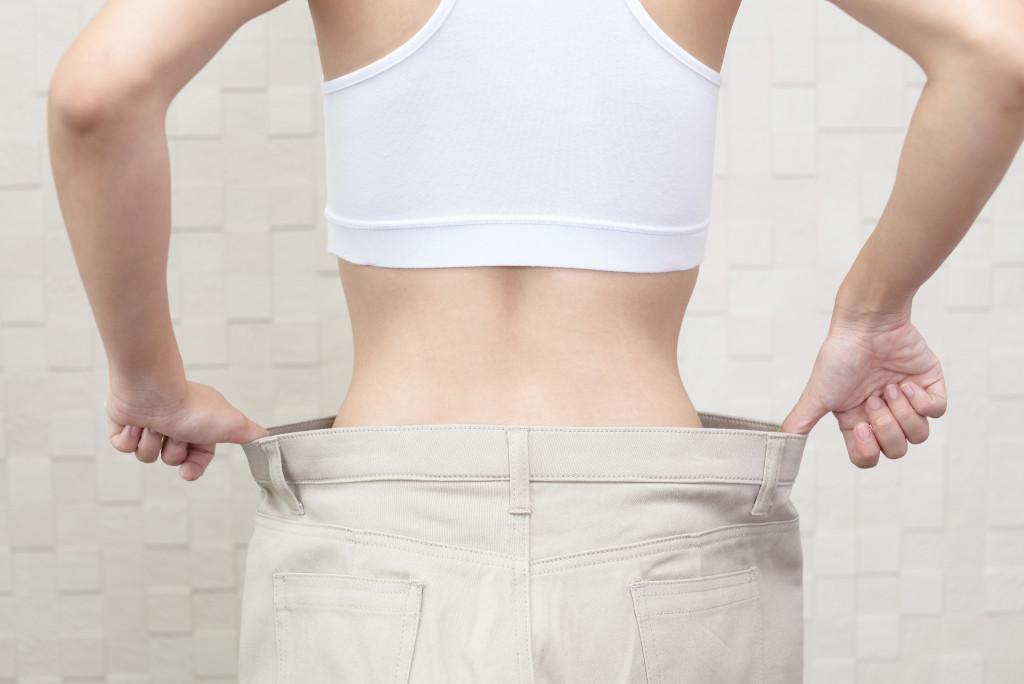 woman holding loose pants