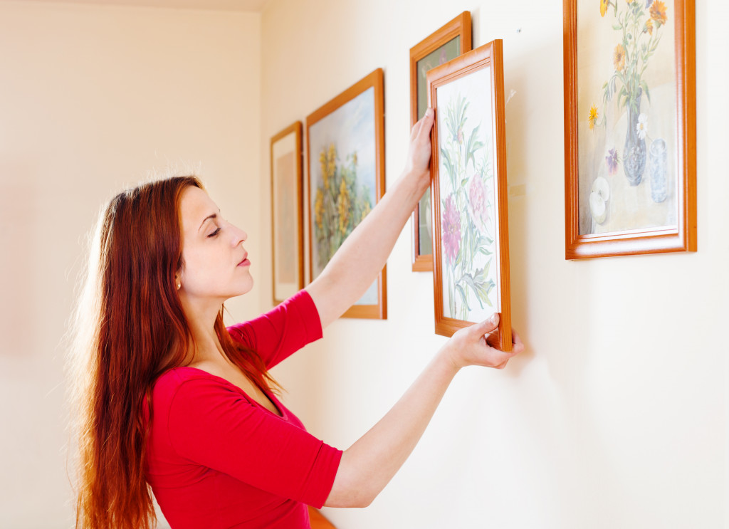 woman hanging paintings