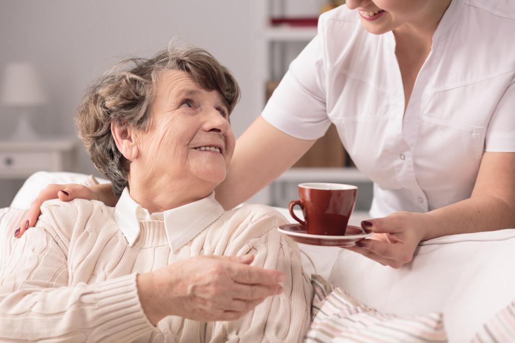 nurse handing a cup to an elderly woman